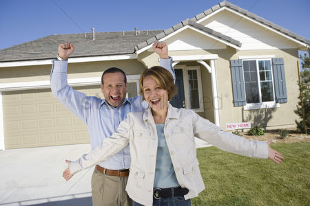 Arm raised : Mid-adult couple celebrating house ownership