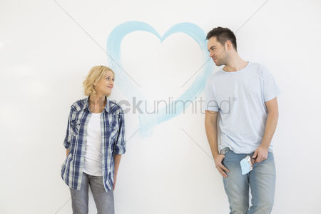 Shape : Mid-adult couple looking at each other with painted heart on wall
