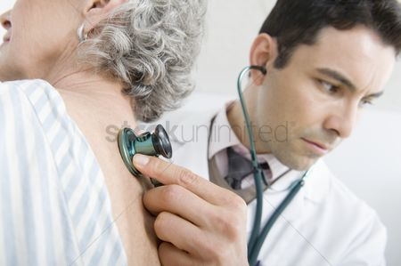 White hair : Mid adult doctor checks breathing of senior patient