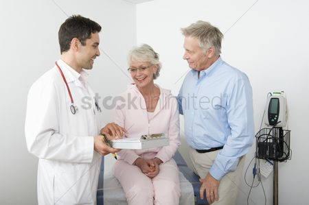 Hispanic : Mid adult doctor explains test results to senior couple