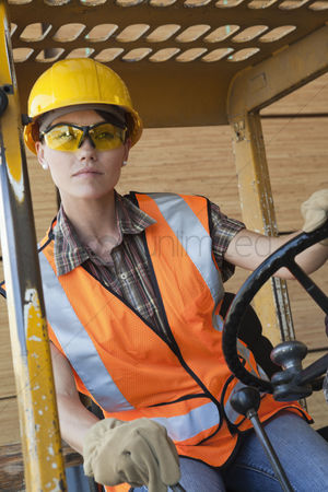 Forklift : Mid adult female industrial worker driving forklift truck
