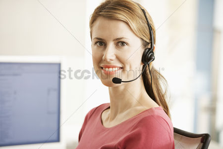 Interior : Mid-adult female office worker sitting in cubicle wearing headset portrait