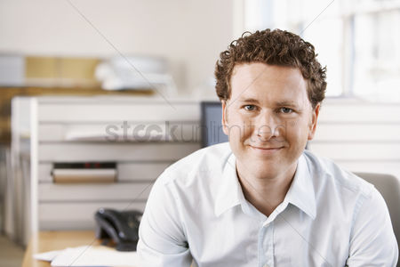 Curly hair : Mid-adult male office worker sitting in cubicle portrait