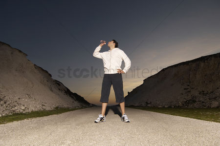 On the road : Mid adult man drinking water after jogging  evening