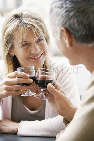 Toasting : Middle-aged couple sitting at outdoor cafe in rome toasting wine glasses close up