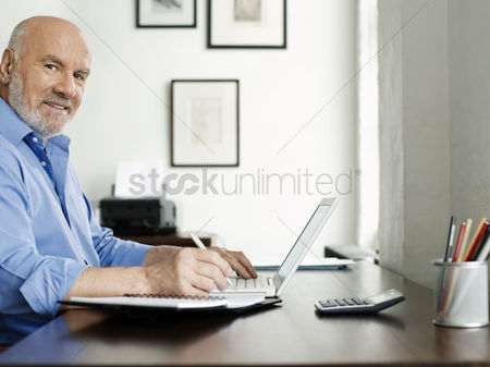 Camera : Middle-aged man sitting at desk using laptop and writing in notepad