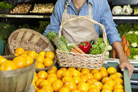 Employee : Midsection of man standing near oranges stall with vegetable basket in supermarket