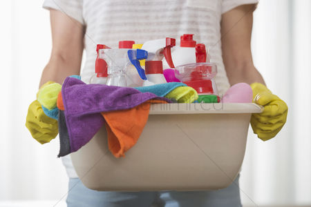 30s adult : Midsection of woman carrying basket of cleaning supplies