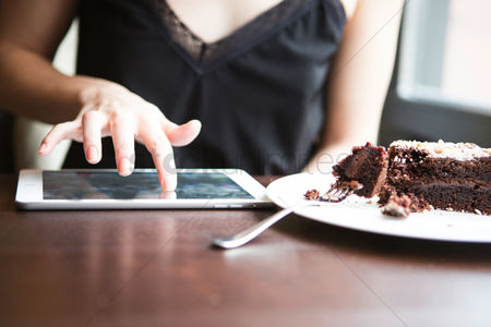Czech republic : Midsection of woman using tablet pc by pastry in cafe