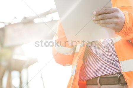 Supervisor : Midsection supervisor holding clipboard at construction site on sunny day