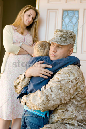 Loss : Military father embracing son  5-6  outside home wife watching