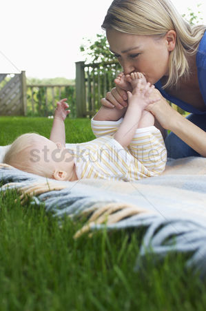 Kissing : Mother and baby lying on lawn in garden