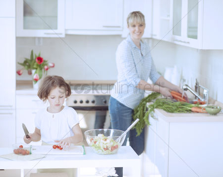 Offspring : Mother and daughter  8-9  preparing healthy meal in kitchen