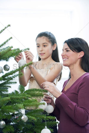 Maturity : Mother and daughter decorating the christmas tree