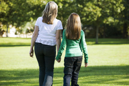 Grass : Mother and daughter holding hands while walking in the park