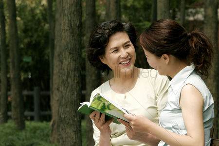Aging process : Mother and daughter looking at photo album together