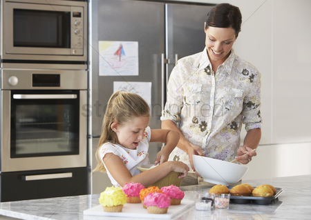 Bowl : Mother and daughter making cupcakes in kitchen