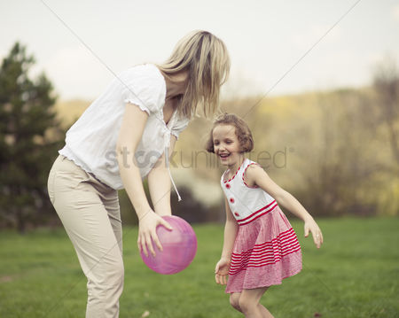 Offspring : Mother and daughter playing with ball in the park