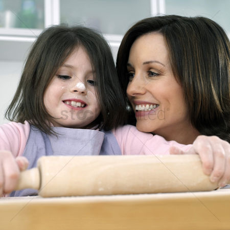 Kid : Mother and daughter rolling dough in the kitchen