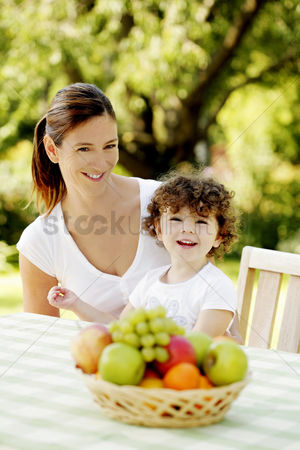 Cheerful : Mother and daughter sitting at the picnic table