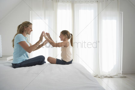 Daughter : Mother and  daughter sitting on bed playing patty cake side view