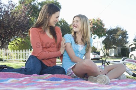 Offspring : Mother and daughter sitting on picnic blanket