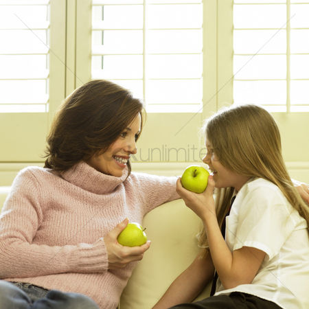 Fashion : Mother and daughter sitting on the couch holding green apples