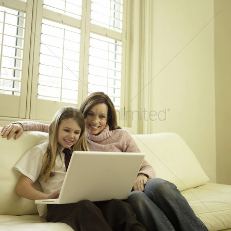 Three quarter length : Mother and daughter sitting on the couch using laptop
