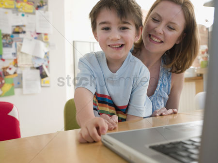 Offspring : Mother and son at table with laptop