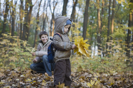 Collection : Mother and son collecting leaves in park