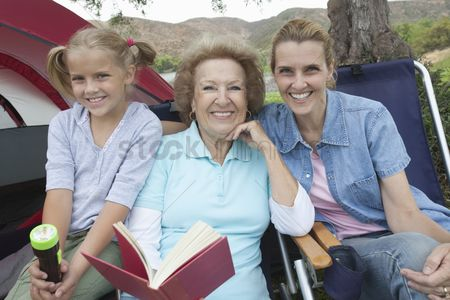 Pitch : Mother daughter and grand-daughter sit reading outside tent
