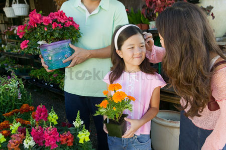 Shopping background : Mother fixing hair of daughter in plant nursery