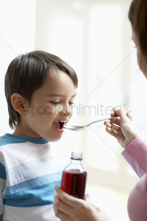 Medication : Mother giving son cough syrup