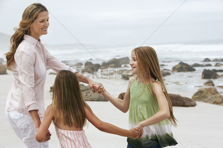 Appearance : Mother playing with two daughters  7-9 10-12  on beach