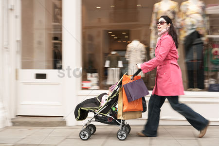 Appearance : Mother pushing stroller by clothes shop on street