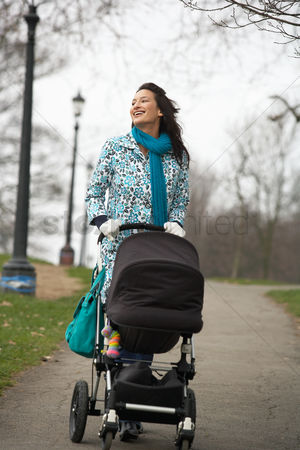 Pushing : Mother walking with baby carriage in park