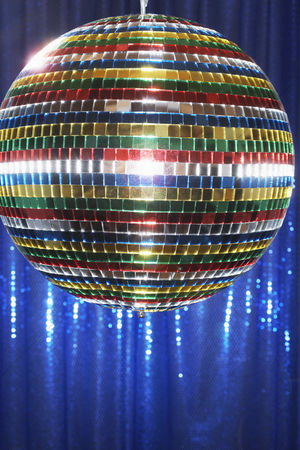 Dance : Multi-coloured disco ball in front of blue stage curtain close up