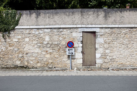 Forbidden : No parking sign against stone wall