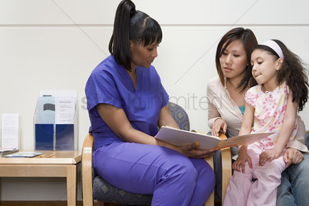 Sitting on lap : Nurse talking to mother and daughter