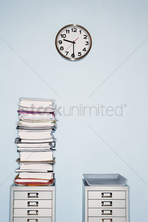 Pile : Office wall with clock stack of paperwork in inbox on file cabinet