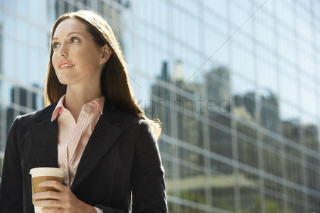 Women : Office worker with drink outside office building portrait