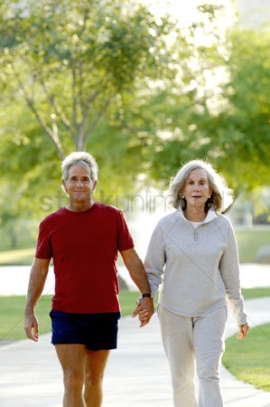 Lover : Old couple holding hands while walking in the park