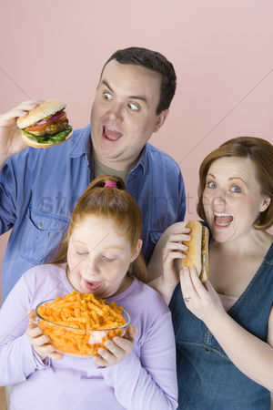 Hot dog : Overweight family holding unhealthy food