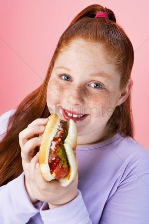 Hot dog : Overweight girl  13-15  eating hot dog portrait close-up