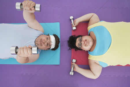 Curly hair : Overweight man and woman lying down lifting dumbbells overhead view