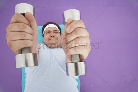 Dumbbell : Overweight man lying down lifting dumbbells overhead view