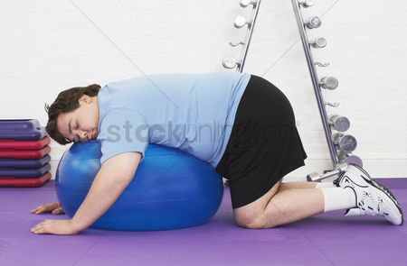 Loss : Overweight man sleeping on exercise ball in health club