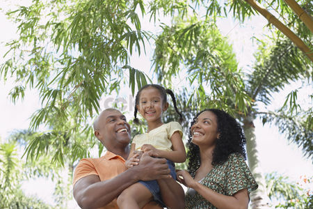 Curly hair : Parents with daughter  5-6 years  in tropical forest low angle view portrait