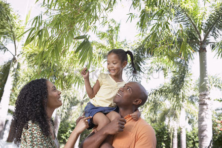 Curly hair : Parents with daughter  5-6 years  in tropical forest low angle view