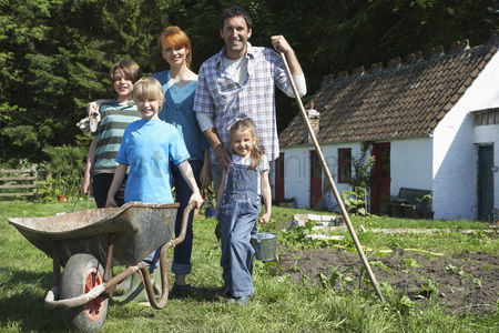 Grass : Parents with three children  5-9  gardening outside cottage portrait